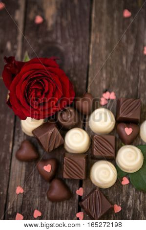 Red roses and sweet chocolates on wooden background with copy space.