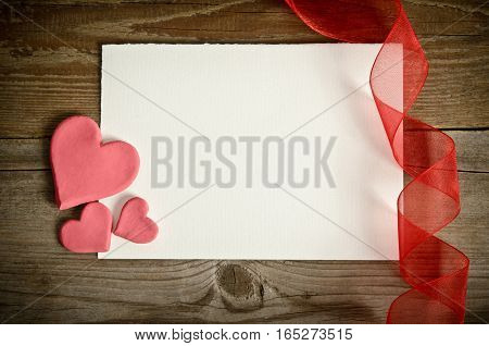 piece of paper lying with hearts and ribbon on a wooden background