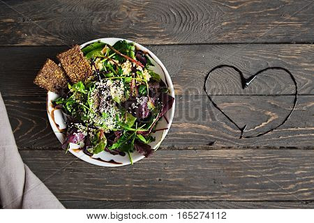 Love fresh green salad with spinach arugula quinoa and flex seed crackers on a dark wooden table. Heart shaped sauce. Healthy food lifestyle concept. Flat lay