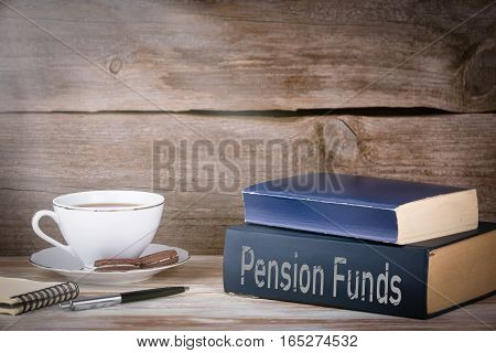 Pension Funds. Stack of books on wooden desk.