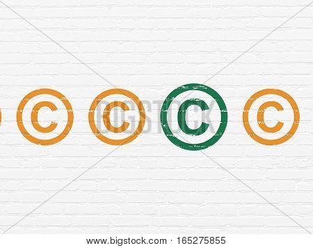 Law concept: row of Painted orange copyright icons around green copyright icon on White Brick wall background