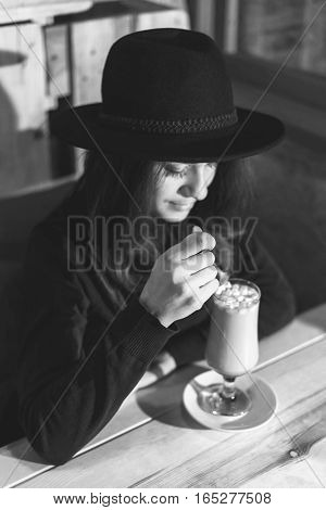 Beautiful young lady in big hat drinking coffe outside in summer cafe