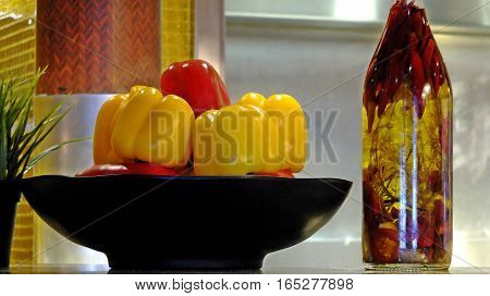 Red and Yellow Bell Peppers in Bowl with Seasoned Olive Oil in Bottle