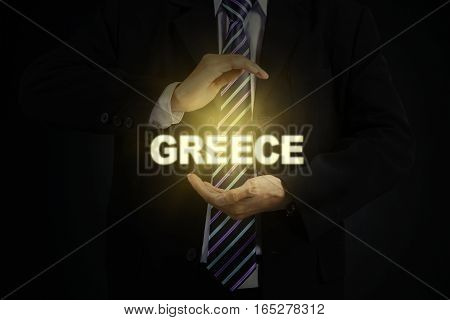 Close up of two arm businessman holding a light of the Greece word