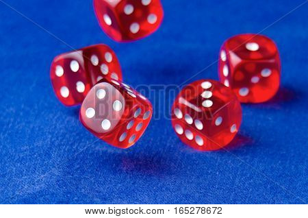 abandoned red dice with white dots on blue canvas. Shallow depth of field