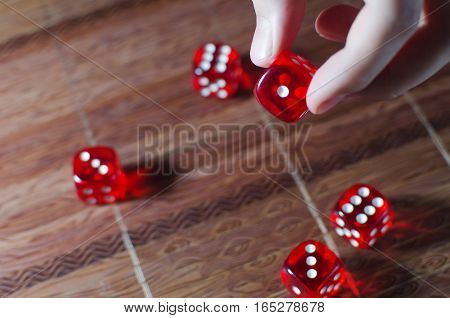 Red dice dice with white dots in hand and lying on the wicker wooden canvas background. Shallow depth of field.