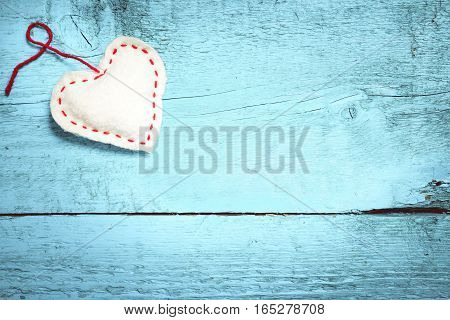 Valentine's Day white heart with red stitching on light blue boards with copy space. Valentine's day card with space for text. Toning in bright colors.