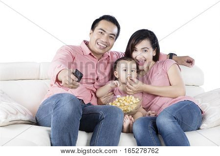 Picture of two young Asian parents and her daughter sitting on the couch while watching TV and eating popcorn