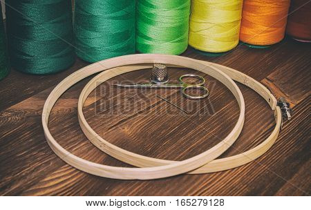 number of colored thread in the coils with wooden hoops for embroidery and needlework vintage toning