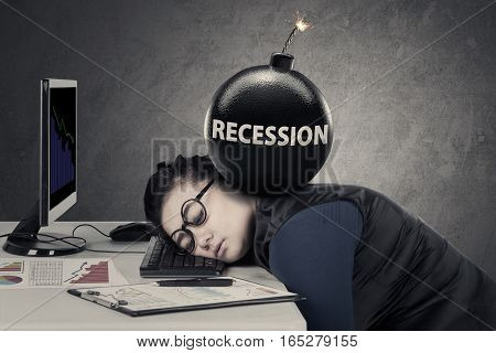 Portrait of young woman sleeps with bomb of recession over her head