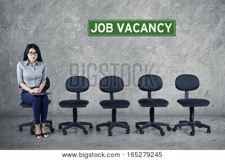Portrait of young woman holding a clipboard while sitting on a chair with empty chairs and text job vacancy on board