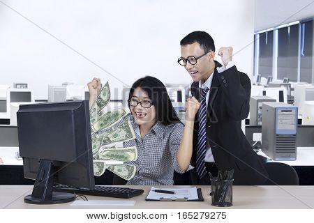 Two young workers looks cheerful looking at dollars banknotes on the computer monitor in the office