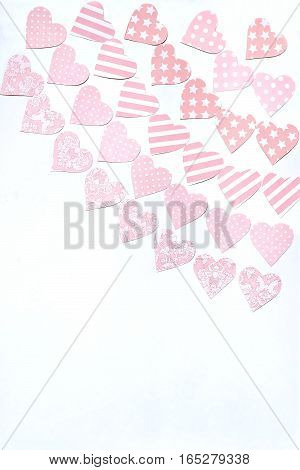 Garlands of tender pink hearts carved by hand from paper with various ornaments. Festive background to Valentines Day with empty space for text