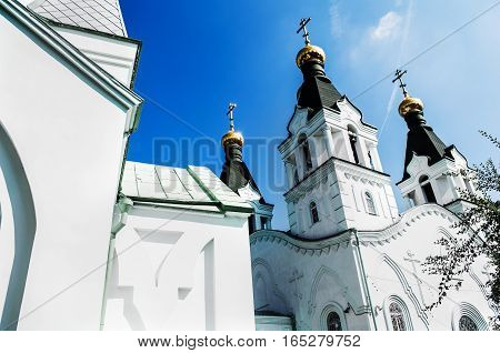Golden dome with a cross of the Russian Orthodox church against the blue sky background