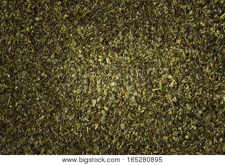 green background of dried chopped herbs spices.