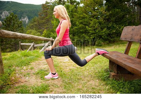 Lunge Step On A Bench - Young Woman Excercising In Nature