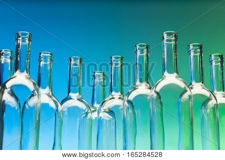 Crystal bottlenecks of empty glass wine bottles standing in a row