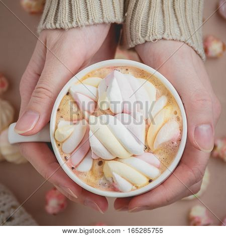 Woman holding cup of hot cacao or coffee on wooden background, Closeup of hands in warm sweaters. Top view