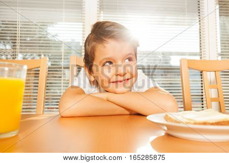 Adorable six years old boy sitting in the kitchen at breakfast