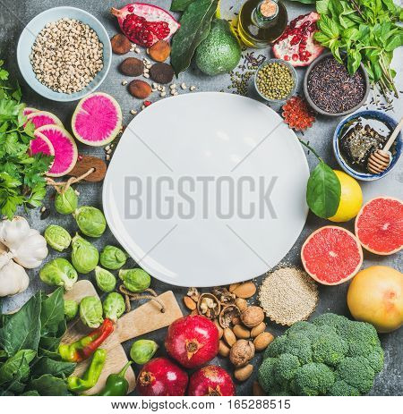 Clean eating concept over grey background with white plate in center, top view, copy space. Vegetables, fruit, seeds, cereals, beans, spices, superfoods, herbs for vegan, raw diet and gluten free diet