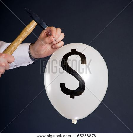 businessman hitting a nail into a white balloon with a dollar symbol