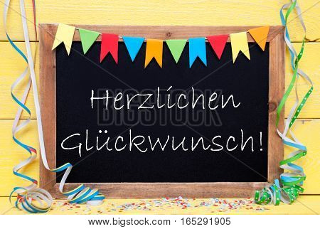 Blackboard With German Text Herzlichen Glueckwunsch Means Congratulations. Party Decoration Like Streamer And Confetti. Yellow Wooden Background. Greeting Card For Celebrations