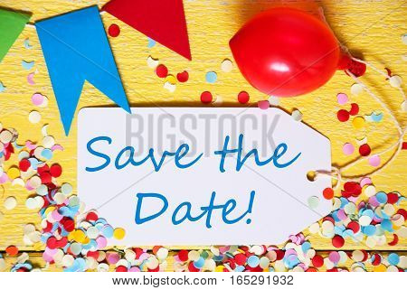 White Label With English Text Save The Date. Close Up Of Party Decoration Like Streamer, Confetti And Balloon. Flat Lay Or Top View. Yellow Wooden Background