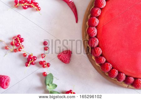 Tart pie cake with jellied and fresh raspberry on the light concrete background. Top view. Sweet food photo concept