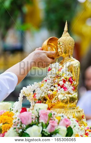 people showering buddha statue on Songkran festival in Thailand ,very shallow depth of field.