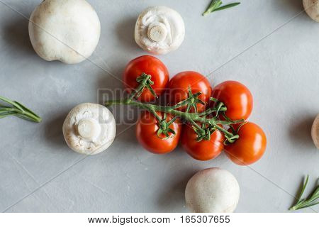 tomatoes on a branch thyme on a gray light background natural light view from above