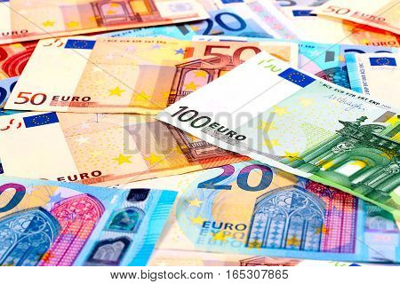 a small pile of paper euro banknotes as part of the European financial and trading system
