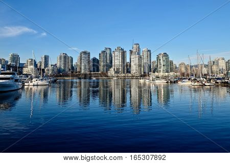 Buildings and boats reflection in calm water of city harbor. Yaletown. False Creek. Vancouver downtown. British Columbia. Canada.