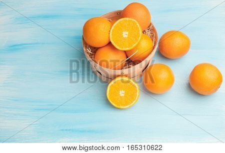 Oranges in a basket on a blue wooden background
