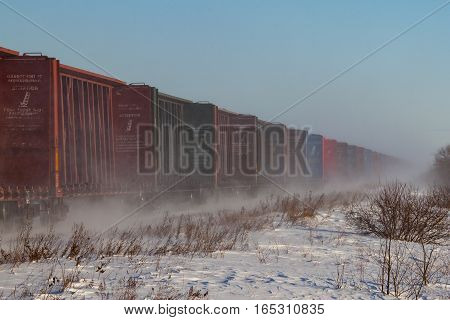 A line of empty lumber railway cars wagons in the winter