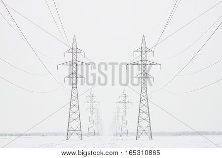 Two lines of transmission towers marching toward the horizon in a white winter scene, horizontal crop