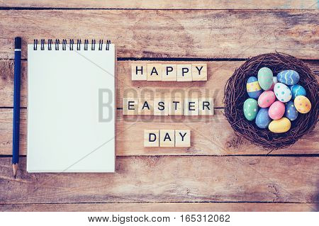 Blank Notebook, Colorful Easter Egg In The Nest And Wood Text For Happy Easter Day On Wood Backgroun
