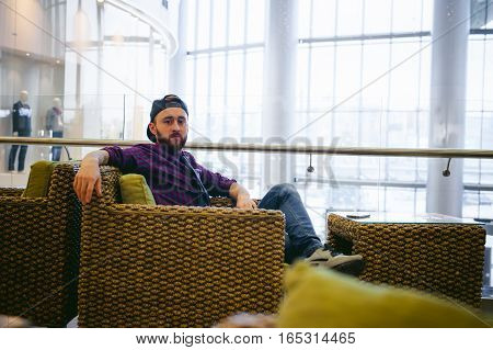 Young Man With A Beard In A Plaid Shirt And A Tie And Cap, Sitting On The Sofa The Coffee Shop In Th