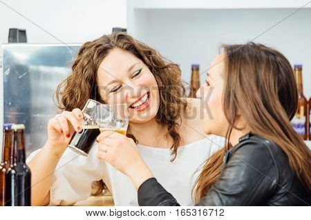 Two laughing women with glasses of craft beer