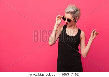 Young beautiful sexy blonde woman in a retro round sunglasses with red sensual lips on pink background with copy space