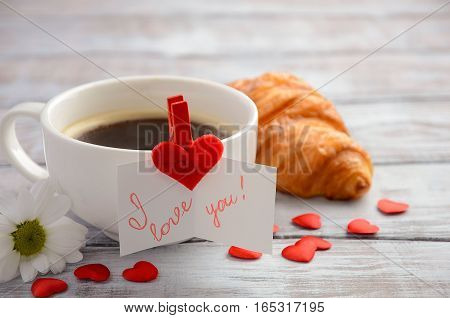 Cup of fresh morning coffee with croissant. Valentine's day concept.