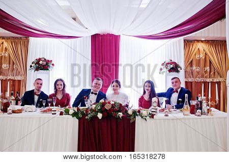 Wedding Couple With Best Mans And Bridesmaids Sitting On Table At Restaurant.