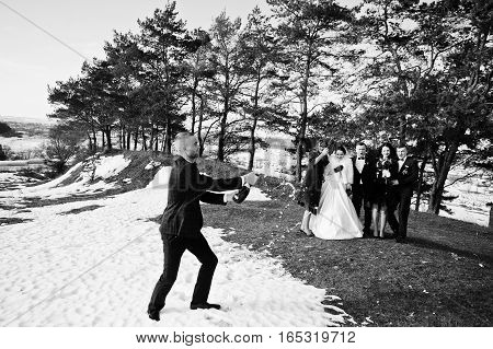 Best Man With Bridesmaids And Newlyweds Drinking Champagne On Frost Winter Wedding Day. Black And Wh