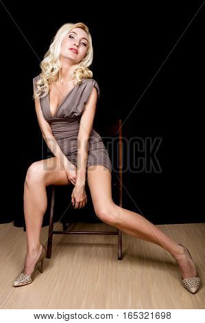 Portrait of a stunning young sexy woman posing in little gray dress.