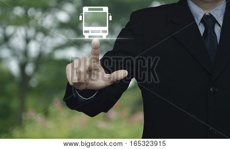 Businessman pressing bus flat icon over blur flower and tree Business transportation service concept