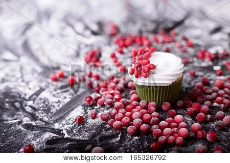 Cupcake with red berries cranberry mountain ash on a dark background