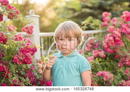 Girl standing on a background of roses. The concept of Allergy