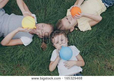 Three Happy Children Playing  On The Grass At The Day Time.