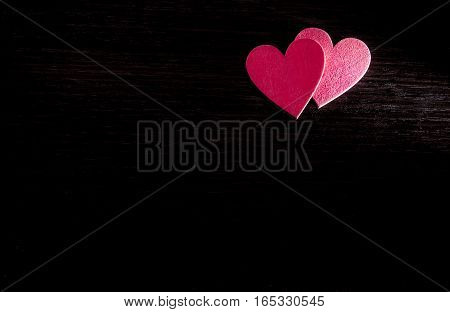 Two red hearts lie on the wooden background