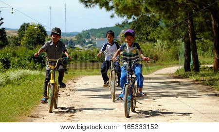 Vietnamese Children Ride Bicycle On Country Road