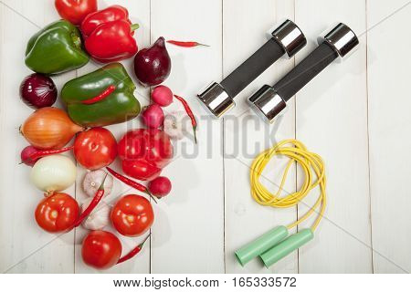 Sport and diet. Healthy lifestyle. Vegetables and dumbbells and. Peppers, tomatoes, garlic, onions and radishes on a white background